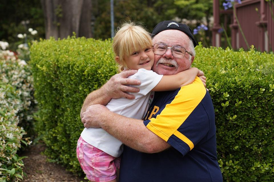 older man hugging child